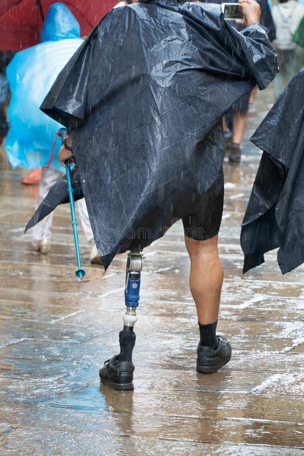 Turístico masculino ativo ou peregrino com prótese caminhando numa rua de uma cidade antiga de Santiago de Compostela num dia chu imagem de stock royalty free
