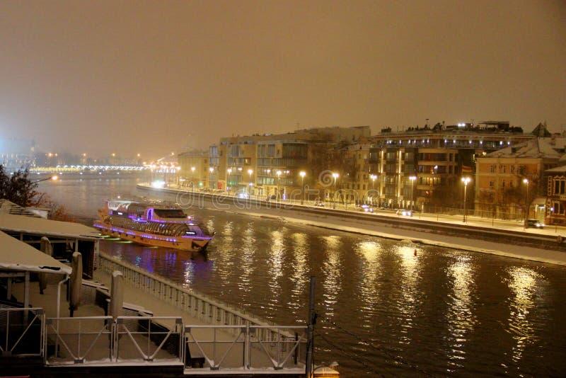 Tur för vinteraftonfartyg på Moskvafloden i snöfallet Nattljus och flodnavigering i en stads- miljö för vinter royaltyfria bilder