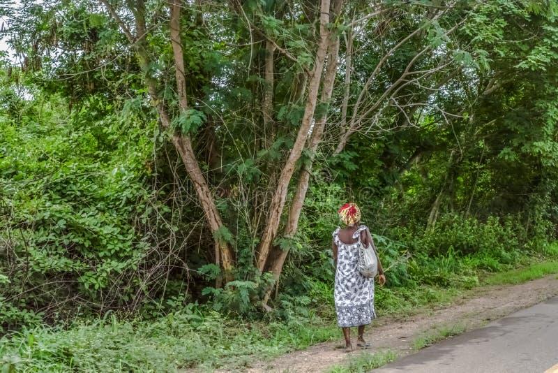 Tur till och med Angola& x27; s-länder 2018: Sikt av kvinnan från baksida som sid av vägen för att gå bakgrund royaltyfria bilder