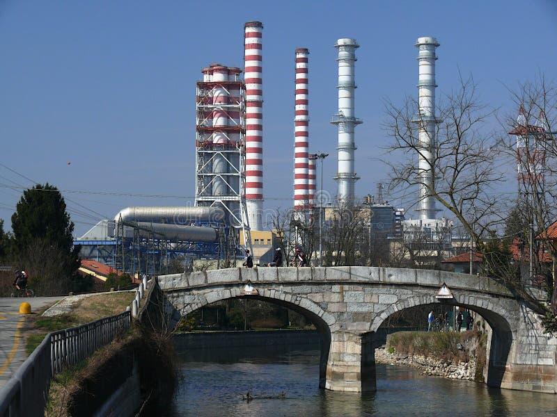 Turbigo, Milaan, 23/03/2009 Elektrische centraleschoorstenen en een kanaalbrug in de voorgrond stock fotografie