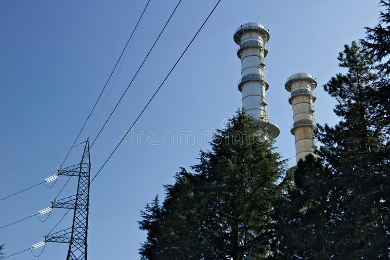 Turbigo milaan Itali? 24 maart, 2019 Schoorstenen en elektrische pylonen achter treesTurbigo royalty-vrije stock foto's