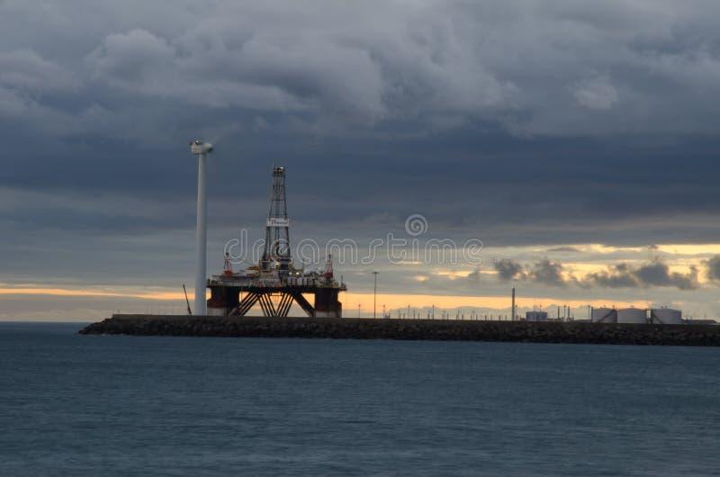 Turbina de la plataforma petrolera y de viento en la puesta del sol imagen de archivo