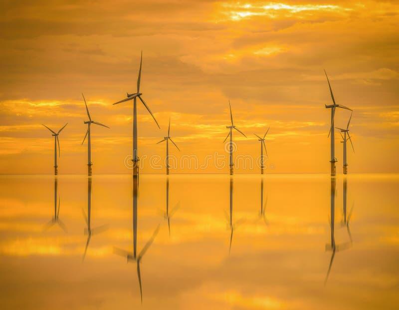 Turbina de viento costero de la puesta del sol en un parque eólico bajo construcción fotos de archivo libres de regalías