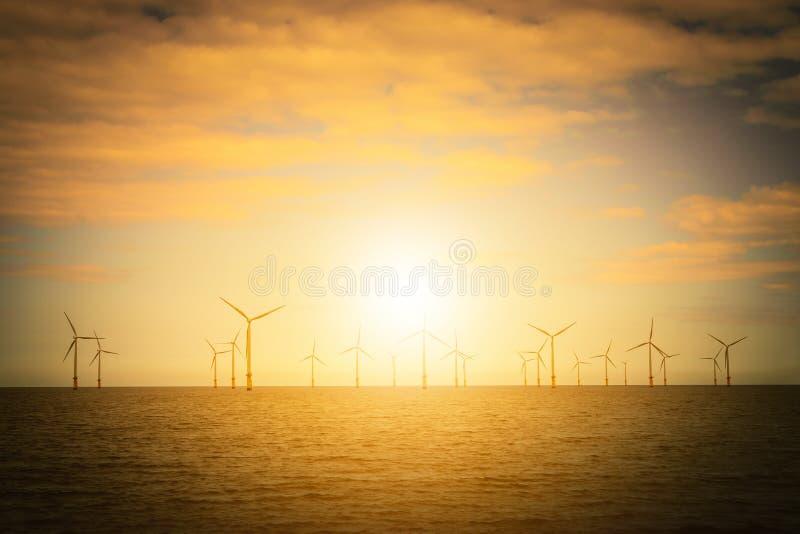 Turbina de viento costero de la puesta del sol en un parque eólico bajo construcción o foto de archivo