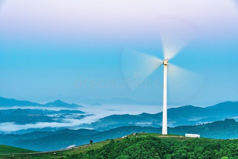 Turbina de viento en la colina en la niebla de la mañana imagen de archivo libre de regalías