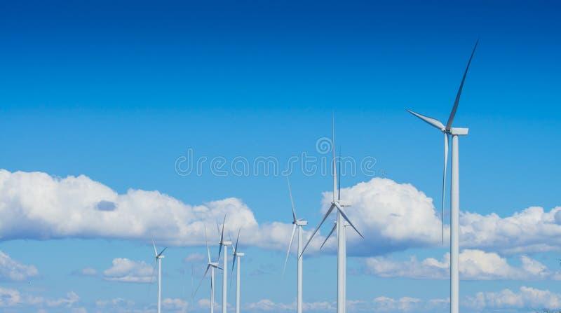 Turbina de viento para la energía alternativa en fondo del cielo azul con las nubes imagen de archivo