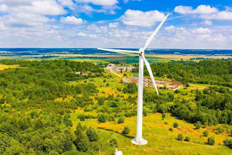 Turbina de viento rodeada por paisaje que sorprende del bosque verde Adultos jovenes Concepto de la energ?a alternativa imagenes de archivo