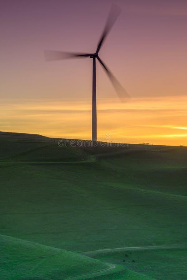 Turbina de viento solitaria que hace girar en una puesta del sol herbosa de la ladera imágenes de archivo libres de regalías
