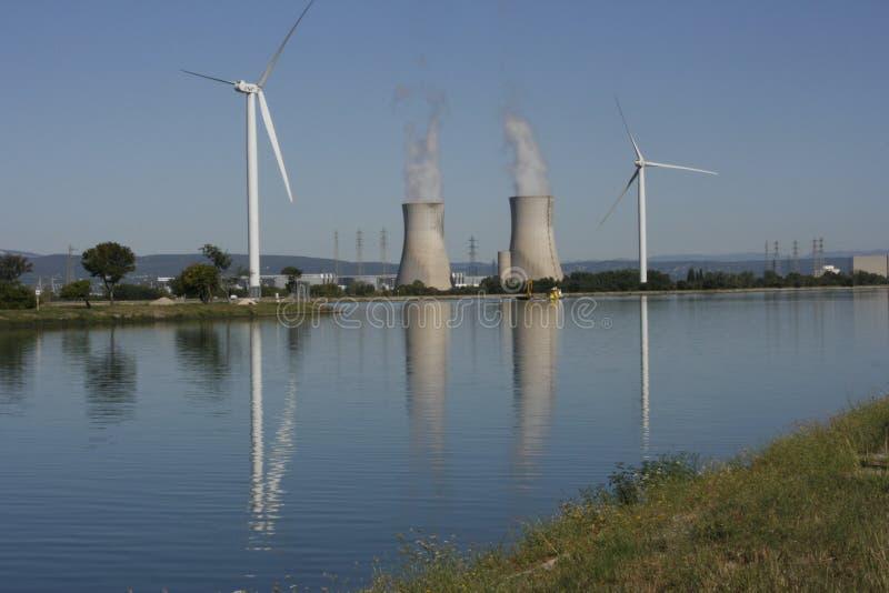 Turbina de viento y torre de enfriamiento nuclear foto de archivo
