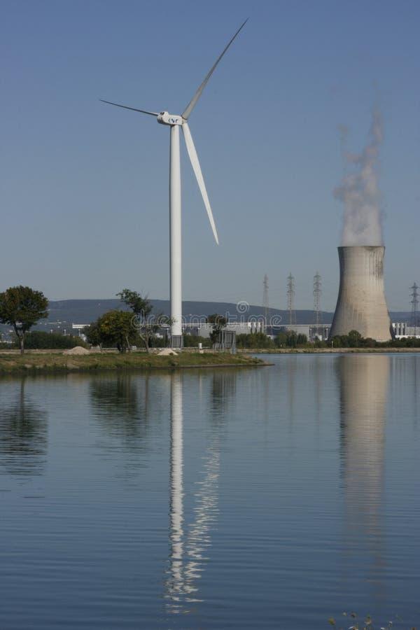 Turbina de viento y torre de enfriamiento nuclear imagen de archivo