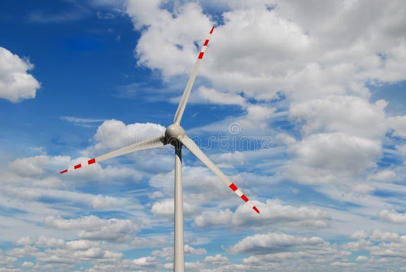 Turbina eólica com as nuvens no céu azul - imagem ilustração stock