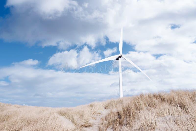 A turbina eólica entre o estorno cobriu dunas imagens de stock royalty free