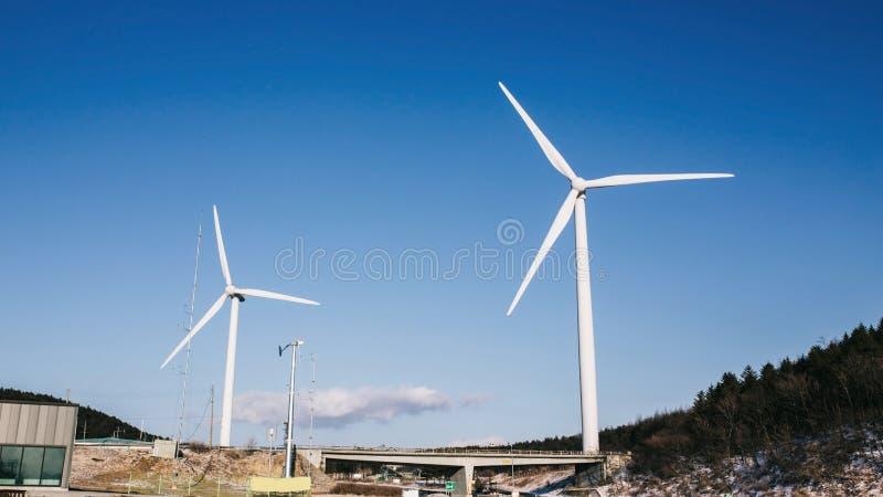 Turbina eólica no campo e no prado na montanha com o céu azul da beleza e fundo nebuloso fotografia de stock