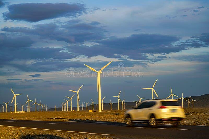 Turbina eólica no por do sol com nuvens bonitas imagem de stock royalty free