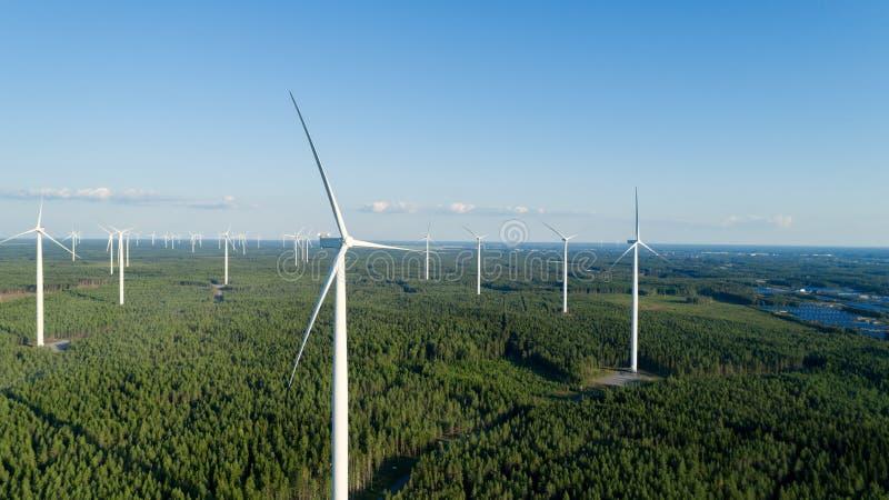 Turbina eólica perto da floresta verde, paisagem aérea bonita com céu azul Produzindo a energia na maneira a favor do meio ambien fotos de stock royalty free