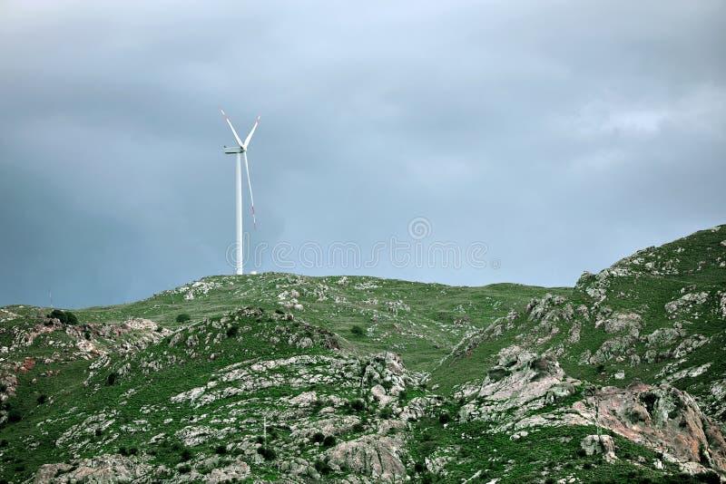 Turbina eólica sobre um cume rochoso coberto com as plantas verdes fotos de stock