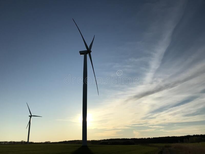 Turbina eolica o eolica con sole tramontato dietro e spazio libero fotografia stock libera da diritti