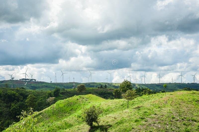 Turbina eolica a vento per energia rinnovabile su paesaggi montani con polo ad alta tensione e polo elettrico sulle colline fotografia stock libera da diritti
