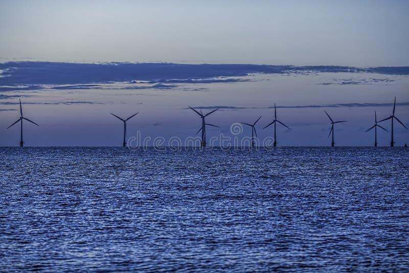 Turbinas costeras del parque eólico entre la noche y el día fotografía de archivo libre de regalías