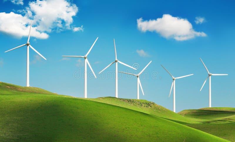 Turbinas de vento em montes verdes imagem de stock