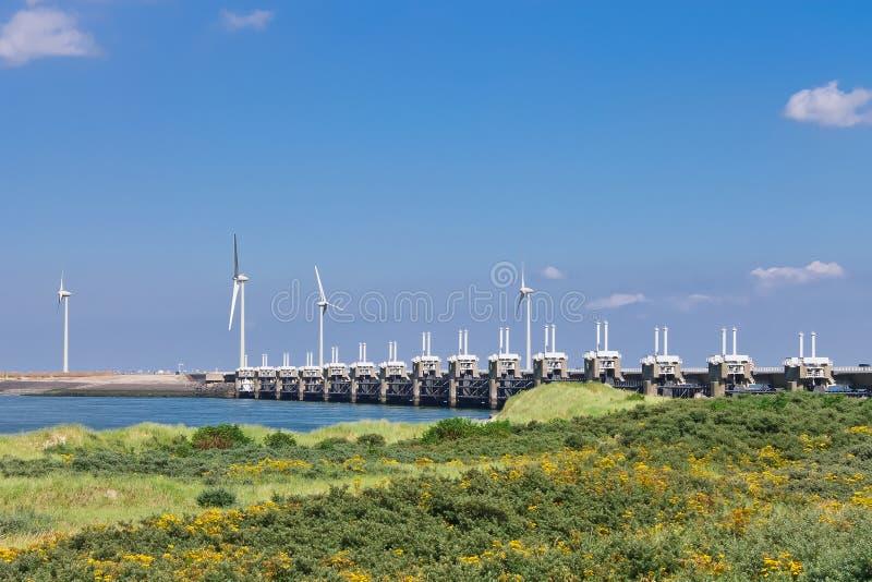 Turbinas de viento cerca de la barrera de la tormenta. imagenes de archivo