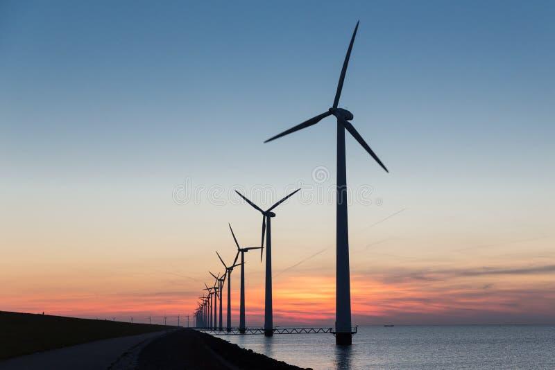 Turbinas de viento costero holandesas de la fila en la puesta del sol hermosa fotografía de archivo libre de regalías