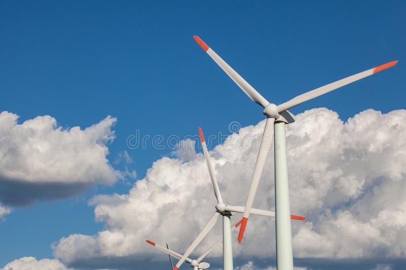 Turbinas de viento en campo verde Cielo nublado azul fotos de archivo libres de regalías