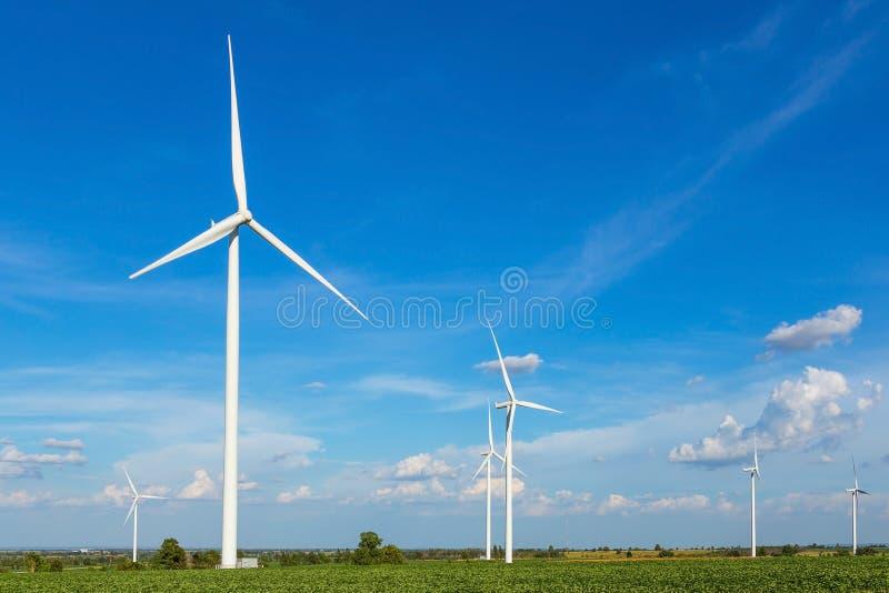 Turbinas de viento en el campo contra el cielo azul que genera electricidad imagenes de archivo