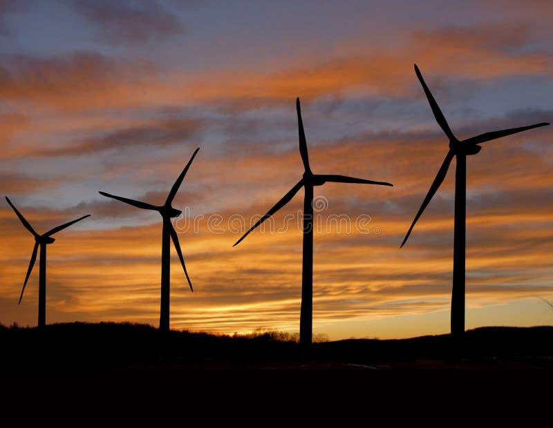 Turbinas de viento en la puesta del sol fotos de archivo
