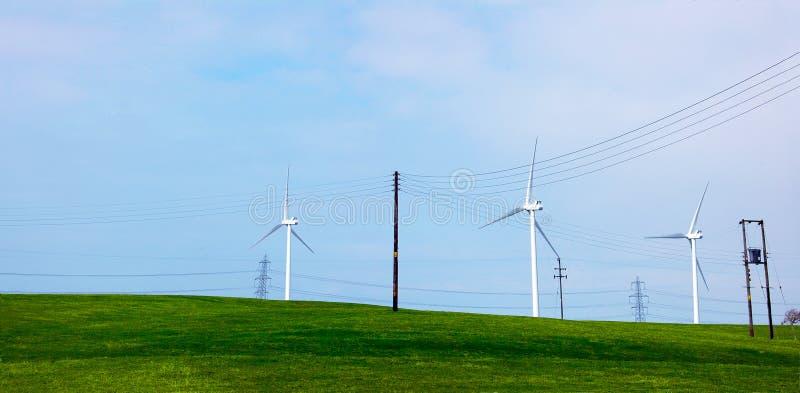 Turbinas de viento en una colina verde fotografía de archivo libre de regalías