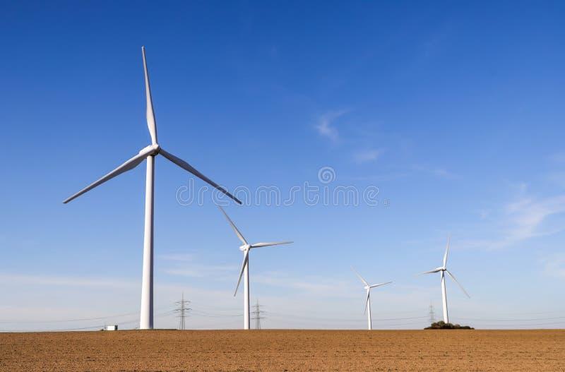 Turbinas de viento que generan electricidad con el cielo azul imagenes de archivo