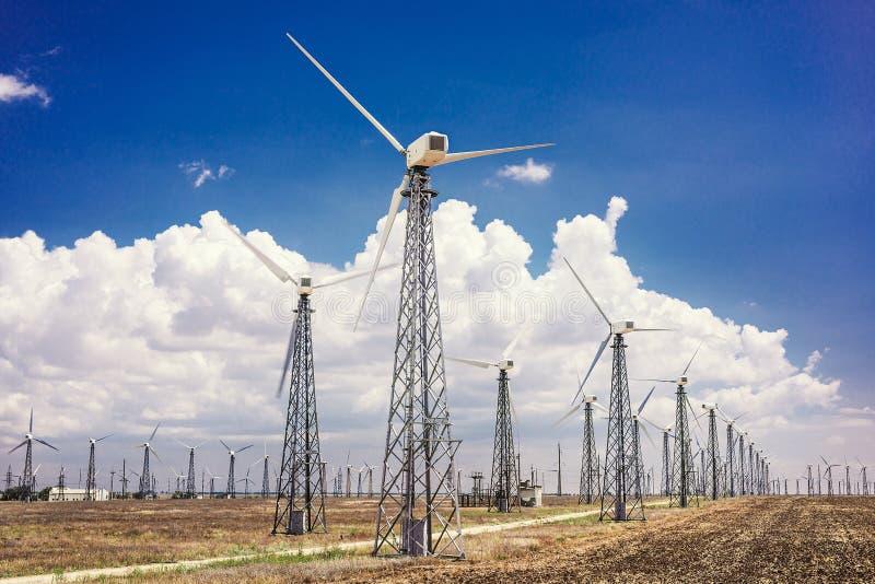 Turbinas de viento que generan electricidad en los campos de Europa foto de archivo