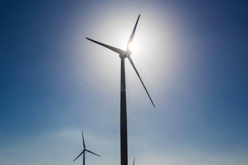 Turbinas de viento que generan la electricidad con el cielo azul - concepto del ahorro de energía fotos de archivo