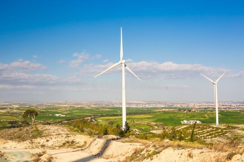 Turbinas de viento que generan la electricidad con el cielo azul - concepto del ahorro de energía imagen de archivo