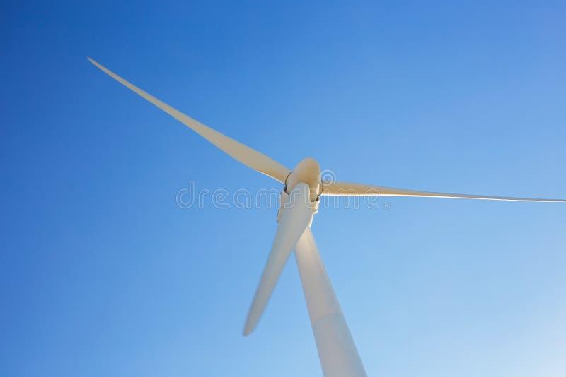 Turbinas de viento que generan la electricidad con el cielo azul - concepto del ahorro de energía foto de archivo