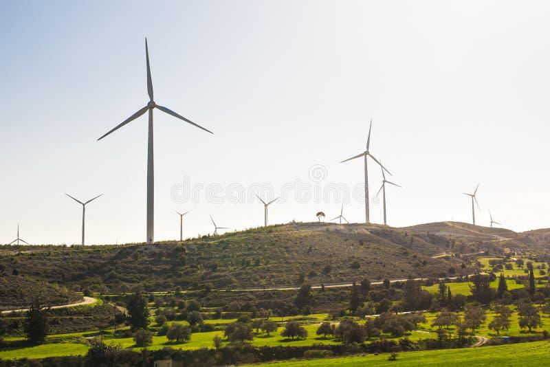 Turbinas de viento que generan la electricidad con el cielo azul - concepto del ahorro de energía fotografía de archivo