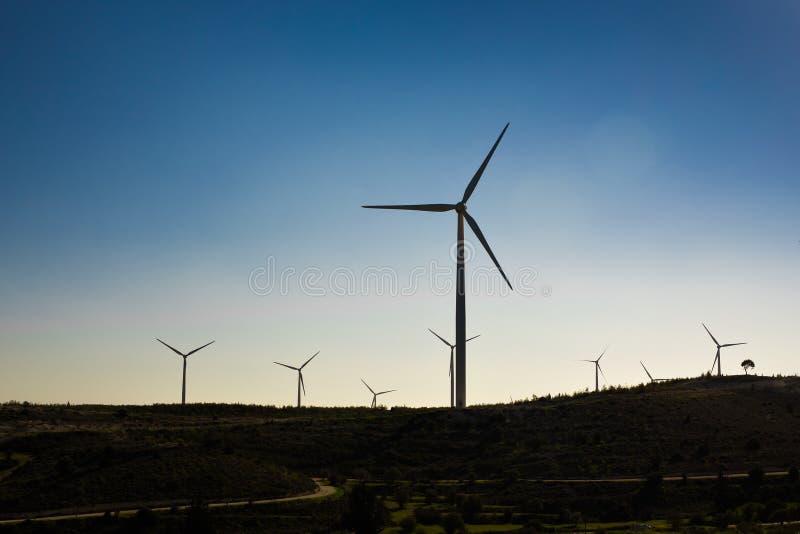 Turbinas de viento que generan la electricidad con el cielo azul - concepto del ahorro de energía imagenes de archivo
