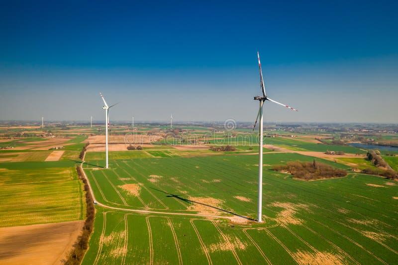 Turbinas de viento quemadas con el cielo azul en un campo verde imagen de archivo