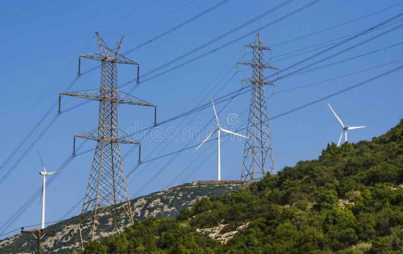 Turbinas de viento y torres de alto voltaje de la electricidad imágenes de archivo libres de regalías