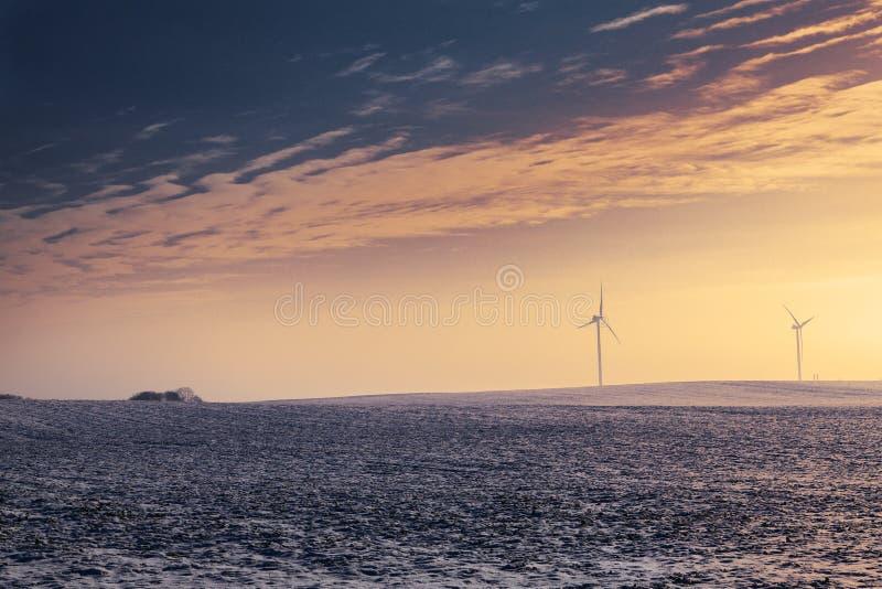 Turbinas eólicas durante o inverno no por do sol fotografia de stock