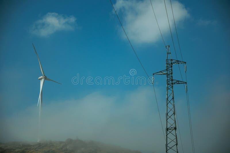 Turbinas eólicas no monte com névoa ao lado da torre elétrica foto de stock royalty free