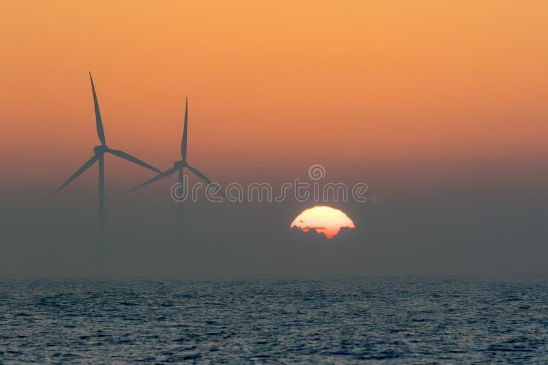 Turbinas eólicas a pouca distância do mar Nascer do sol enevoado do mar da manhã parte traseira tropical imagens de stock royalty free
