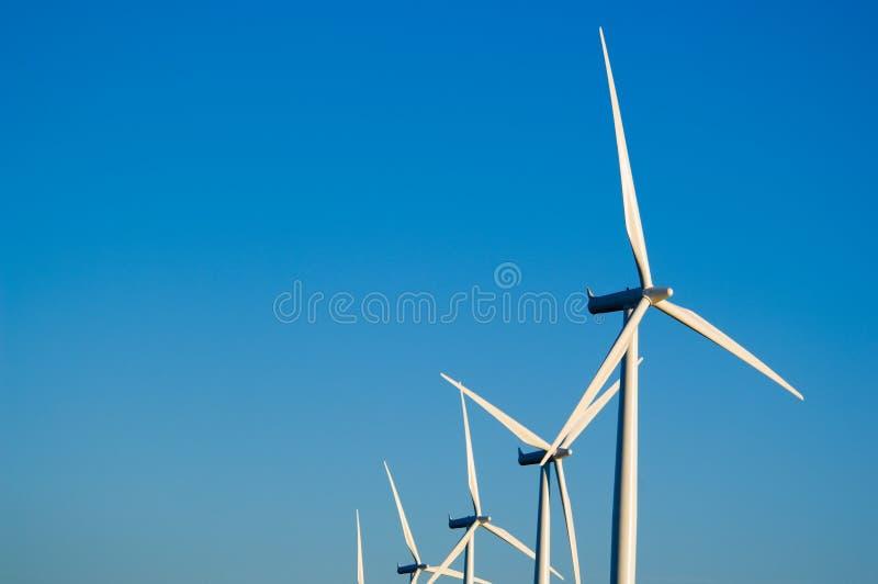 Turbinas ou moinhos modernos de vento que fornecem a energia foto de stock