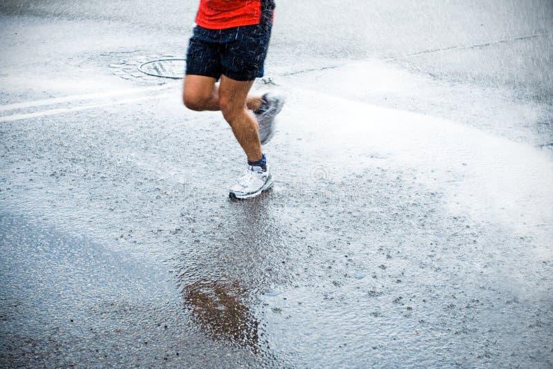 Turbine de marathon sous la pluie sur des rues de ville photo stock
