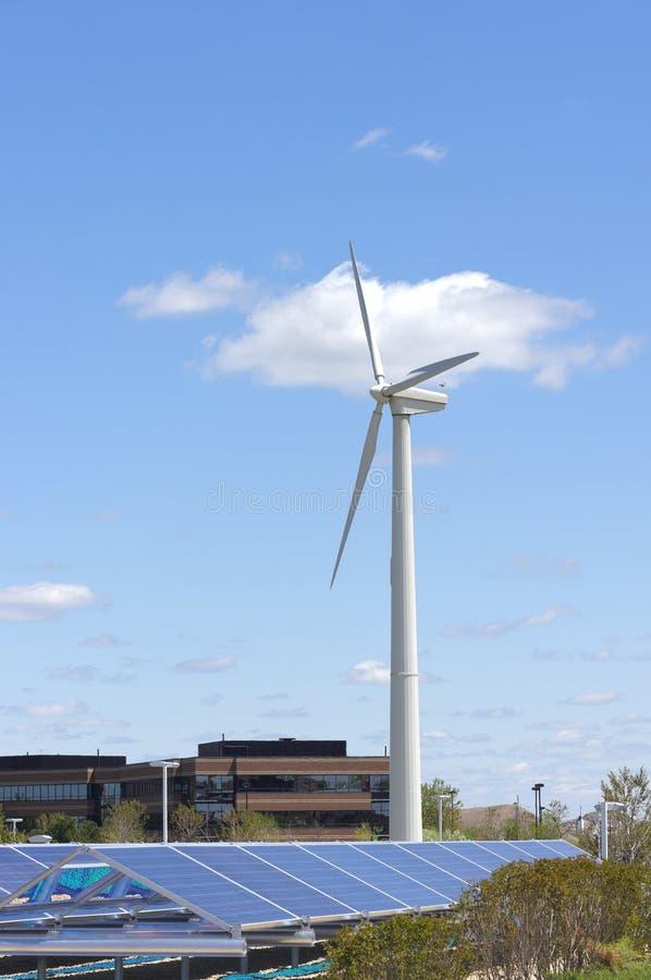 Turbine de vent se levant au-dessus de la rangée solaire images stock