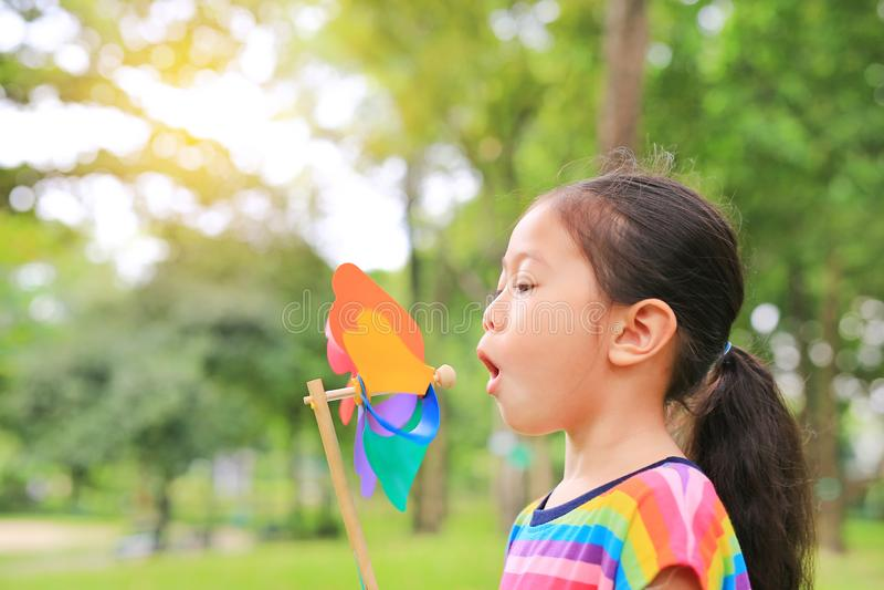 Turbine de vent de soufflement de petite fille asiatique adorable d'enfant dans le jardin d'été image libre de droits