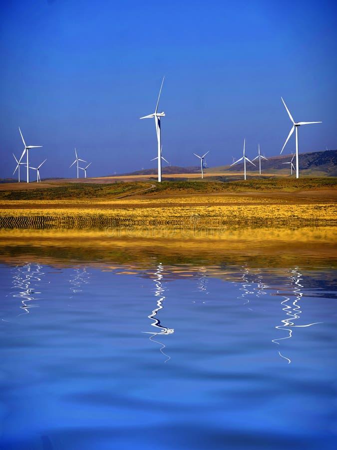 Turbine di energia eolico dei mulini a vento con la riflessione dell'acqua sotto un cielo blu del cobalto fotografia stock