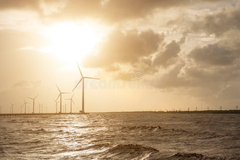 Turbine di vento al tramonto Vento di ecologia contro il backgro del cielo nuvoloso immagine stock