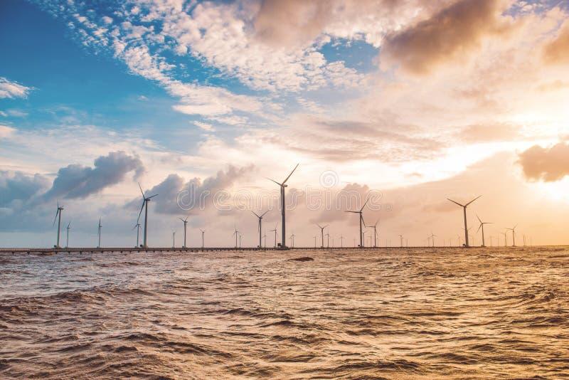 Turbine di vento al tramonto Vento di ecologia contro il backgro del cielo nuvoloso immagini stock libere da diritti