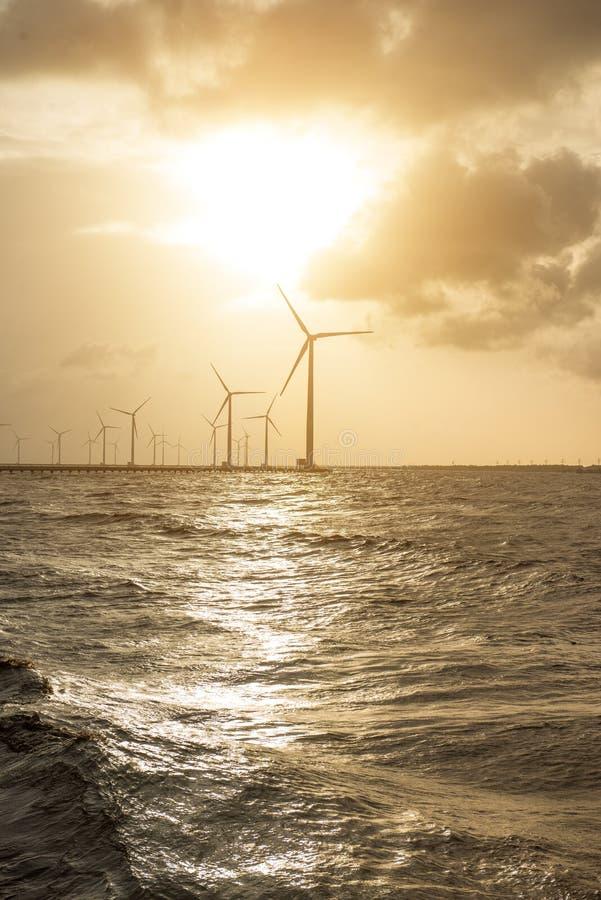 Turbine di vento al tramonto Vento di ecologia contro il backgro del cielo nuvoloso fotografia stock libera da diritti